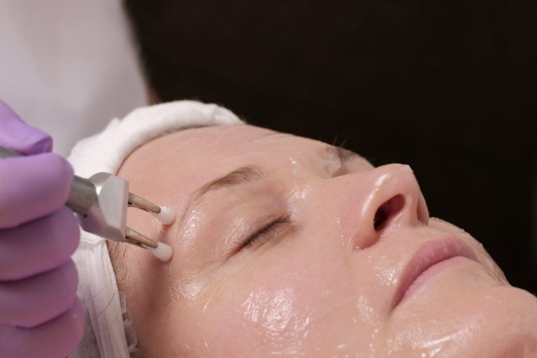Cosmetic procedure for the rejuvenation of the skin with the use of electrodes of a microcurrent apparatus. The hands of a beautician in lilac gloves. Close-up of a female head in a beauty salon.